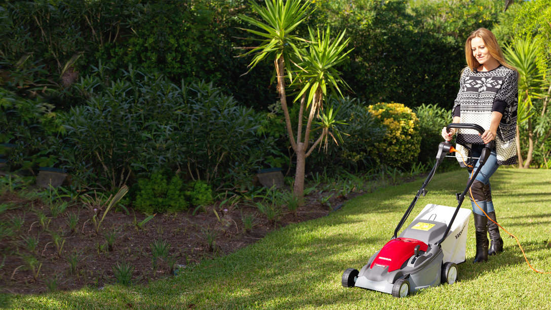 Honda HRE-Rasenmäher, Dreiviertelfrontansicht, nach links zeigend, Einsatz nach Modell, Gartenumgebung.
