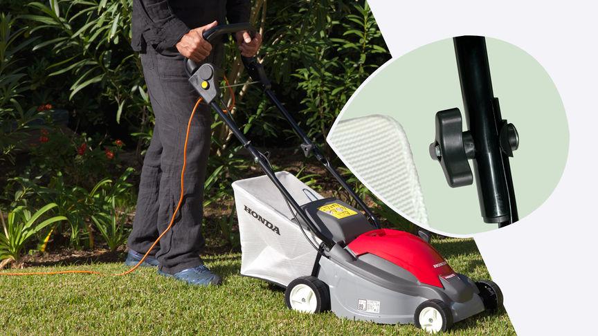 Honda HRE-Rasenmäher, Dreiviertelfrontansicht, nach rechts zeigend, Gartenumgebung. Nahaufnahme des klappbaren Holms.
