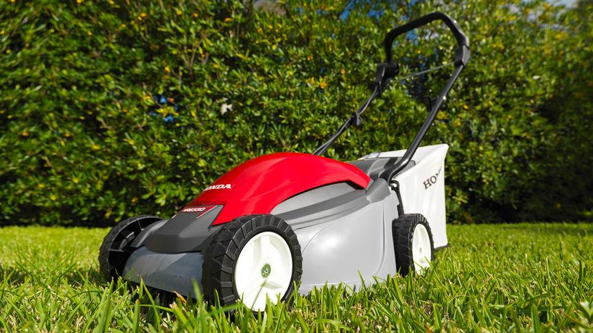 Honda HRE-Rasenmäher, Dreiviertelfrontansicht, nach links zeigend, Gartenumgebung.