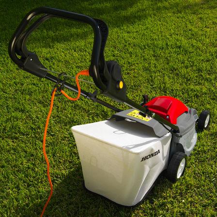 Honda HRE-Rasenmäher, Dreiviertelrückansicht, Kabel im Fokus, Gartenumgebung.