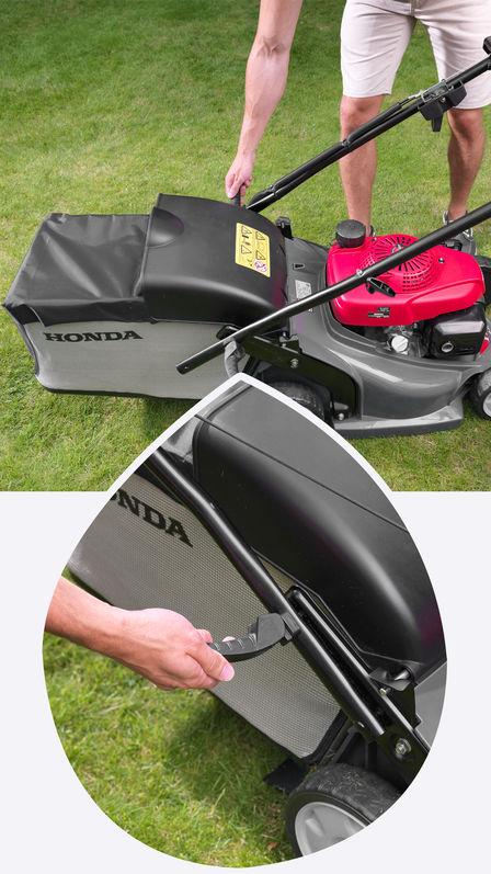 Honda HRX-Rasenmäher, Seitenansicht, nach rechts zeigend, Hebel im Fokus, Gartenumgebung.