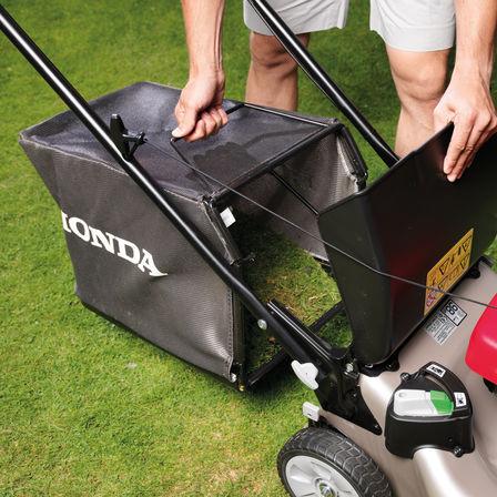 Honda IZY-Rasenmäher, Nahaufnahme von Grasfangsack, Gartenumgebung, nach rechts zeigend.