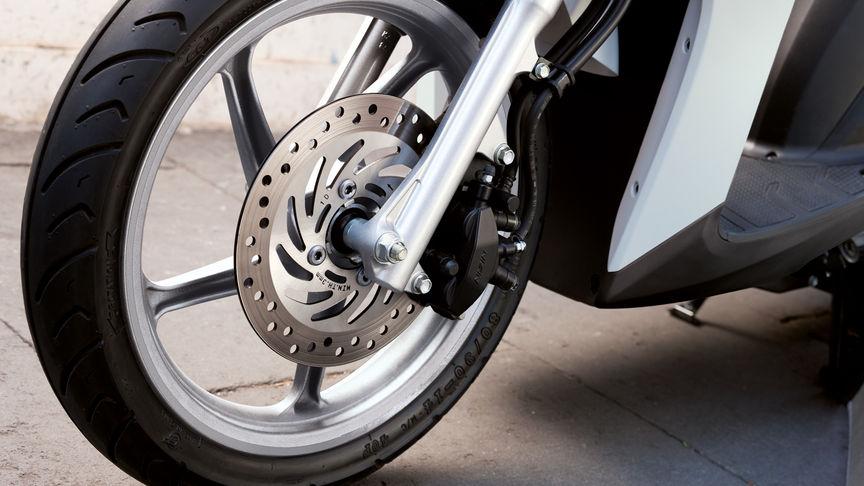 Das Vorderrad des Honda Vision Rollers mit Fokus auf die CBS-Bremsen.