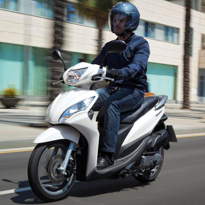 3/4-Frontansicht eines weißen Honda Vision Rollers mit Fahrer. Nach links weisend (auf der Straße).
