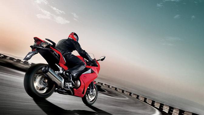 3/4-Frontansicht eines schwarzen Honda SH Mode-Motorrollers mit Fahrer. Nach rechts weisend (auf der Straße).