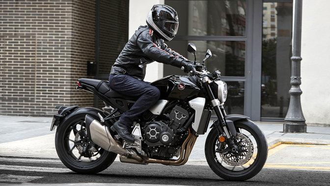 Seitenansicht des Fahrers einer Honda CB1000R Neo Sports Café vor einem Gebäude