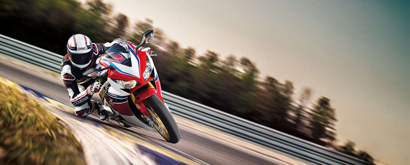 Honda CBR1000RR motorbike front-threequarter view with rider, leaning into bend. Left-facing (Race track location).