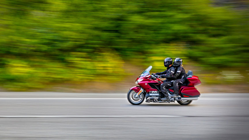 Side facing Honda Gold Wing with rider and pillion.